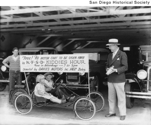 Two children sitting in a motor cart parked in front of a line of automobiles