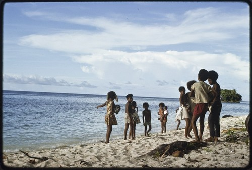 Children, several carrying infants, play on beach