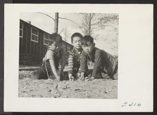 If he's a boy in America he plays marbles, as these lads of Japanese parentage are doing at the Rohwer Relocation Center. Photographer: Parker, Tom McGehee, Arkansas