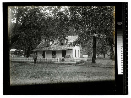 [Man standing in front of fenced house at Hoopa Valley Reservation]