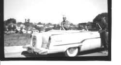Group of young people with a light colored Lincoln Continental convertible car on Willow Street east of High Street in Sebastopol, about 1950s