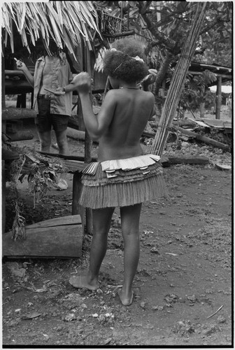 Adolescent girl, wearing short fiber skirt, Edwin Hutchins (in background) holding pen and notebook