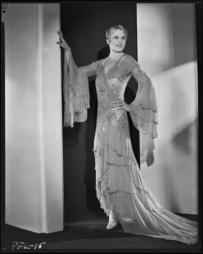 Peggy Hamilton modeling a Travis Banton hostess gown with beaded chiffon and gold lace, 1932