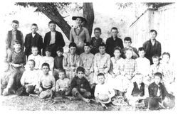 Unidentified group of elementary students with teacher, probably from a rural school, about 1900