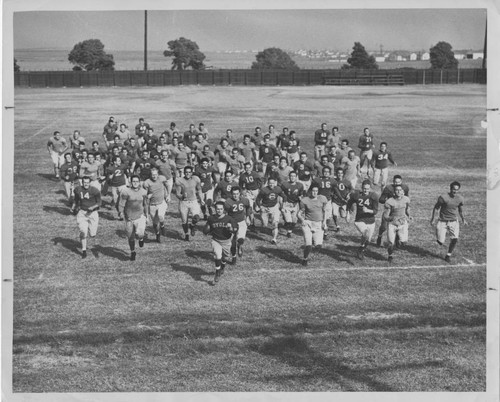 Football team running on field