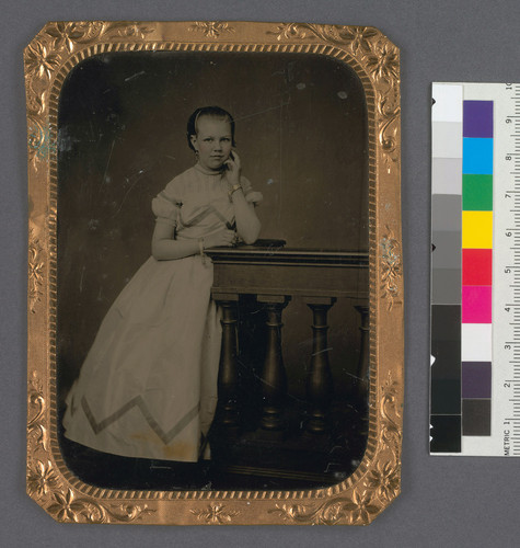 [Full length portrait of Maye C. Bourn, standing, with hand at cheek.]