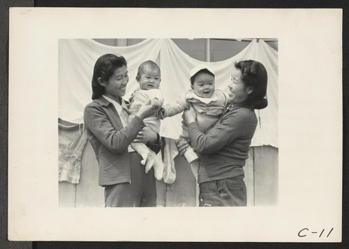 Arcadia, Calif.--Evacuee mothers, with their babies, getting acquainted at the Santa Anita Assembly center where evacuees from this area are awaiting transfer to a War Relocation Authority center to spend the duration. Photographer: Albers, Clem Arcadia, California
