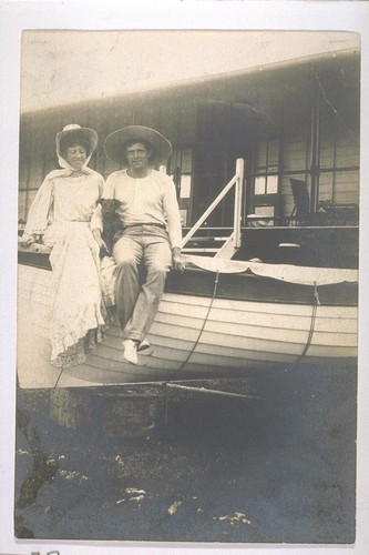 [Jack and Charmian London with dog, sitting on boat.]