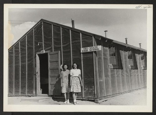 One of the high school buildings with high school graduates (L. to R.) Sakiko Suyama and Chizuko Ishida. Photographer: Cook, John D. Newell, California