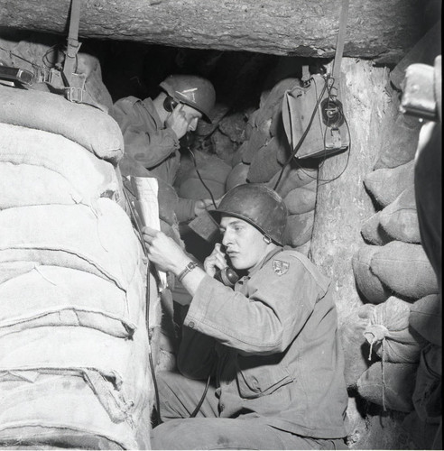 Soldiers calling on field telephones from a bunker