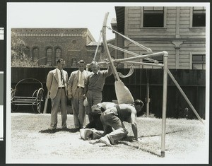 University of Southern California football coaches watch while two men try out a fixed position football training apparatus, Bovard Field, 1934