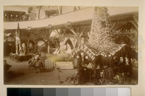 "[Room of flower-covered structures for an exhibition, one labeled ""Long Beach""]"