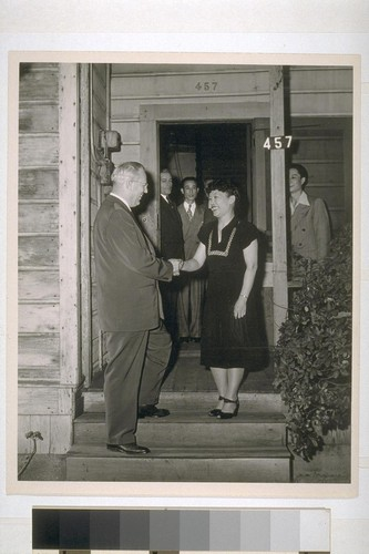 As Governor Earl Warren returns for a visit to his birthplace in Los Angeles, [he] is greeted by the wife of family currently occupying house