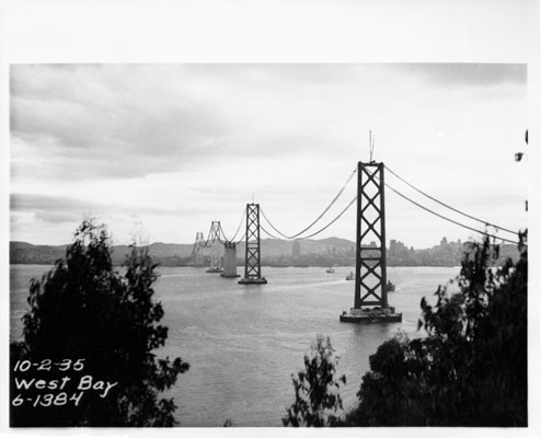[View of catwalk of San Francisco-Oakland Bay Bridge stretched out over the bay during construction]