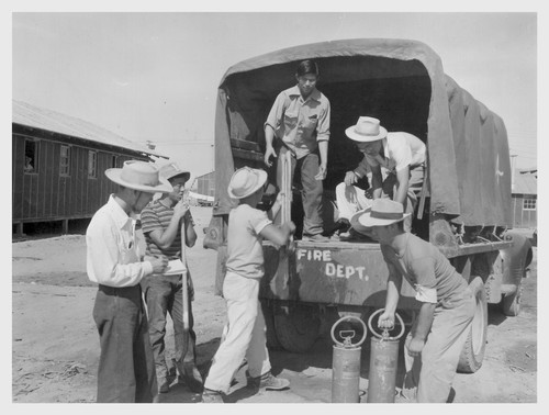 Poston, Ariz.--Evacuee fire truck crew prepare for eventualities at this War Relocation Authority center for evacuees of Japanese ancestry.--Photographer: Clark, Fred--Poston, Arizona. 5/25/42