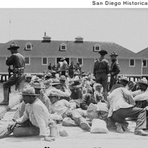 Mexican refugees sitting on a dock near a boathouse under the guard ...