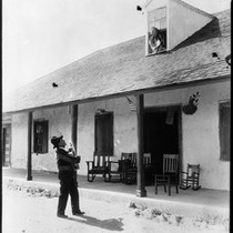 Abram Ontivares serenading his wife Petra outside of the Ontivares adobe, ca.1925