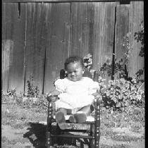 Baby girl sitting in rocking chair in backyard
