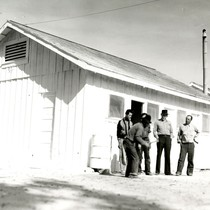 Five Mexican workers standing in front of labor camp buildings, Salinas, California