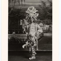 Actor in role of a gallant with an elaborate headdress holds a ...