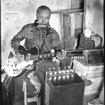 Blues musician Jesse Fuller playing the fodella in his basement
