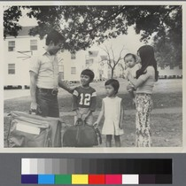 Family with three children holding suitcases