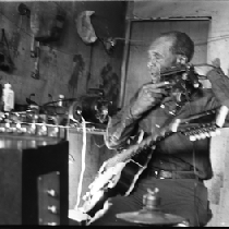 Blues musician Jesse Fuller preparing to play the fodella in his basement