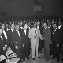 Al Fulcher (left) shaking hands with man surrounded by group of masons ...