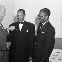 Al Fulcher (center) shaking hands with man
