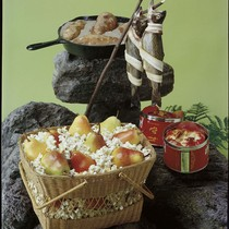 A basket of popcorn with pears, two trout and a cast iron ...