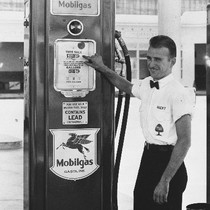 A gas station attendant standing next to a gas pump