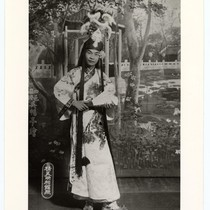 Actor as a scholar in classical costume with elaborate headdress holding a ...