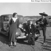Two women sitting on the front of an automobile while being serenaded ...