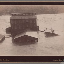 [Flooded buildings, with men on roof of one building.]