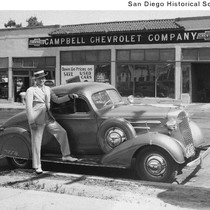 Larry Imig standing next to a Chevrolet automobile parked in front of ...