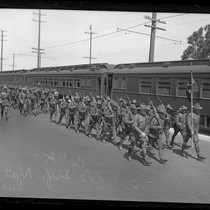 160th Infantry of California National Guard marching besides train in Los Angeles, ...
