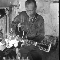 Blues musician Jesse Fuller playing guitar in his basement