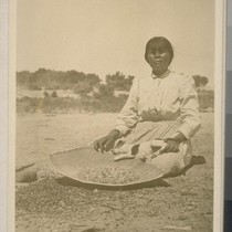Woman cleaning pine nuts; 1 print, 1 negative