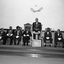 Al Fulcher speaking at podium with masons seated on stage
