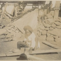 [Indian laborer sawing wood at base of the Pierson telescope in Camp ...