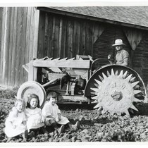 Man and girls posing with a tractor
