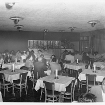 Men and women seated at white cloth-covered tables in open dining area ...