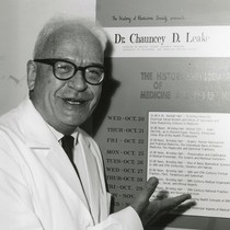 Chauncey Depew Leake in front of History of Medicine Society event poster