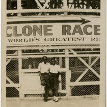 African American couple posed in front of the Cyclone Racer, Long Beach, ...