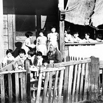 Children and woman on porch