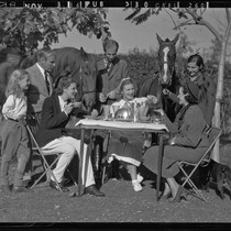 Actress Elissa Landi, family members, and friends having breakfast outdoors with horses ...