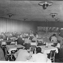 Men and women seated at white-cloth covered tables in one of dining ...