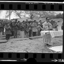Buddhist priest Tri Sanh leading Vietnamese refugees in prayer at Camp Pendleton, ...