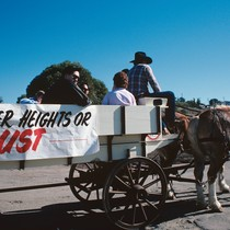 "Slide of horse-drawn wagon with sign reading ""Pioneer Heights or Bust."""