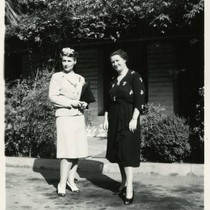 1940, Two Library Staff Standing in Front of a Brick Building